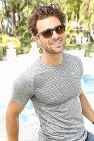 Junger Mann mit Sonnenbrille in grauem T-Shirt