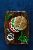 Healthy vegetarian sandwich with feta cheese, tomatoes, basil and pepper served on wooden chopping board over vintage background
