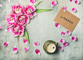 Cup of coffee, pink tulips, petals and sign reading 'Happy'