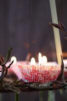 Hängender Adventskranz aus Ästen dekoriert mit Kerzen in Papierförmchen (Nahaufnahme)