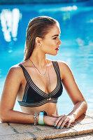 Junge Frau in schwarzem Bikinioberteil im Pool