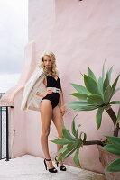 Blonde, langhaarige Frau in schwarzem Badeanzug auf der Terrasse