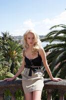 Blonde, langhaarige Frau in schwarzem Top und hellem Rock auf der Terrasse