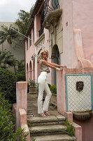 Blonde, langhaarige Frau in sandfarbenem Top und weißer Hose auf der Treppe