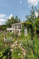 Gewächshaus aus alten Fenstern im Naturgarten