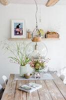 Herbstdeko mit Hagebuttenzweigen und Buch auf Holztisch, darüber Pendelleuchte mit Glasschirm in ländlichem Esszimmer