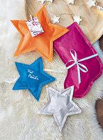 Aus Geschenkpapier genähte Tütchen in Stern- und Stiefelform