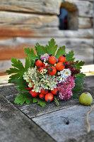 Herbststrauß mit Hagebutten, Hortensie und Fetthenne in Blättermanschette