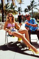 Junge blonde Frau in Bikini sitzt auf einem Stuhl und spielt mit einem äteren Herren Karten