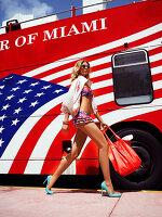 Junge Frau in kurzem, sommerlichen Outfit geht an einem Bus vorbei