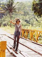 Junge blonde Frau in durchsichtiger Hose und Shirt mit Hut und Halskette