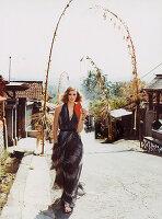 Junge Frau in langem Sommerkleid mit Federdruck