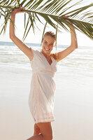 Blonde Frau mit Palmenzweig in weißem Kleid am Meer