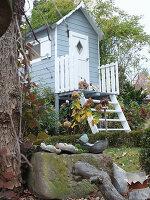Holzhäuschen mit Treppe in herbstlichem Garten