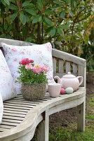 Korb mit Ranunkeln und ein Teegedeck auf einer Gartenbank