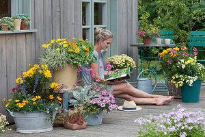 Bunte Sommerterrasse mit Stauden und Sommerblumen, Frau genießt den Sommer