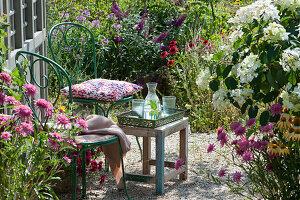 Stühle auf Kiesterrasse am Gartenhaus, Sonnenhut 'Butterfly Kisses' und Conetto 'Banana', Strauchhortensie