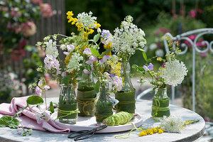 Wiesenblumen in hübsch verkleideten Flaschen