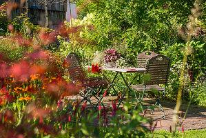 Sitzgruppe auf kleiner Terrasse geschützt zwischen Beeten