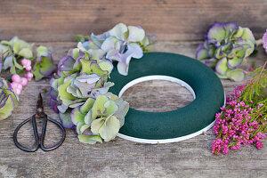 Zutaten für Herbstkranz: Feuchtsteckring, Hortensienblüten, Topferika, Schneebeere und Schere