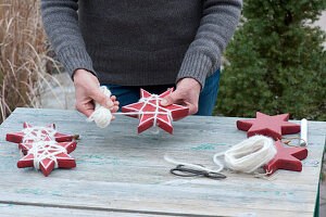 Frau umwickelt rote Holzsterne mit weißer Wollschnur