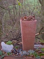 Terracotta-Kübel mit Herbstlaub im winterlichen Garten