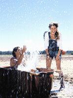 A young man in a bathtub splashing a young woman