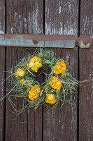 Kranz aus Rosenblüten und Gräsern als Türkranz
