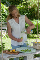 Frau füllt Gläser mit Mineralwasser, frische Minze und Orangenscheibe, Orange und Limette