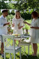 Freunde stehen am gedeckten Tisch, als Vorspeise gibt es Mozzarella-Tomaten-Spieße und Brotstangen