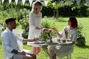 Freunde am gedeckten Tisch im Garten, Frau reicht Brot