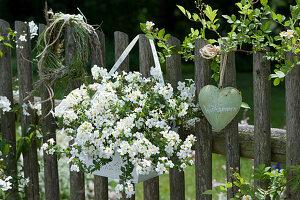 Schneeflockenblume, Metall-Herz und Graskranz als Willkommen am Zaun