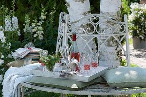 Weißes Tablett mit Strauß aus Walderdbeeren, Besteck und Servietten, Rosato in Flasche und Gläsern auf Baumbank