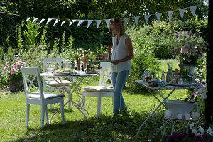 Frau deckt den Tisch im Garten