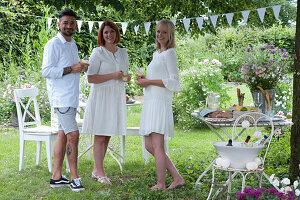Freunde stehen neben dem gedeckten Tisch im Garten