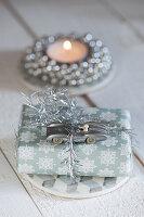 Weihnachtsgeschenk mit silbernem Rennauto als Dekoration