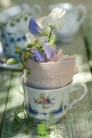 Kleine Tasse mit Duftwicken in Serviette