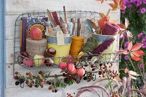 Wandhänger zum Aufbewaren von Utensilien: Bindegarn, Stecketiketten, Kleingerät und Buch, Zieräpfel und Brombeerzweig als Deko