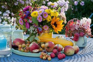 Bunte Tischdekoration mit Sträußen aus Chrysanthemen, Sommerastern, Sonnenblume, Hortensie, Fetthenne und Zierapfel, Äpfel, Zieräpfel und Zucchini auf Tablett