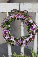 Frühlingskranz aus Hyazinthenblüten, Waxflower, Mimose und Buchs an Stuhllehne gebunden