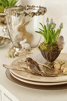 Osterdeko mit Traubenhyazinthen in Silberbecher, Ostereiern, Vögelchen, Silberbesteck und Osterhasen