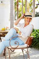 Blonde Frau mit Strohhut in weißem Hemd und hellblauer Hose