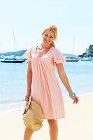 Blonde Frau im rosa Sommerkleid am Meer