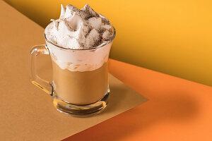 Ein Glas Kaffee Latte mit Schlagsahne und Zimt