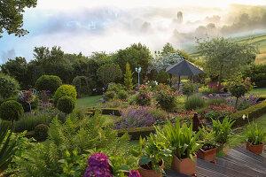 Blick von oben auf Hanggarten mit Pavillon und Beet mit Rosenstämmchen, eingefasst mit Buchshecke