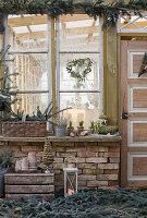 Weihnachtliche Dekoration mit Fichtenzweigen, Eukalyptus-Herz, Mini-Tannenbaum, Laterne und Moosstiefel