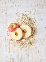 Rohe Apfelringe und Haferflocken auf Holzuntergrund