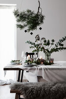 Weihnachtliche Tischdekoration mit Kiefernzweig und Strauß aus Eukalyptus und Mannstreu