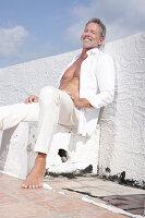 Grauhaariger Mann in weißem Hemd und weißer Hose