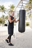 Grauhaariger Mann in schwarzer Sportbekleidung am Boxsack